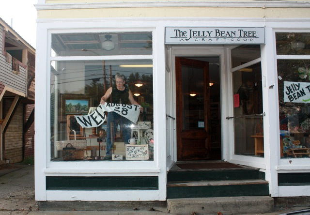Ellen Allman takes down the last window sign before the store opens.